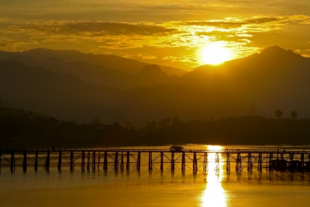 Paisaje vista de la silueta del puente a trav�s del r�o con la luz del sol de oro reflexivo Foto de archivo - 14492157