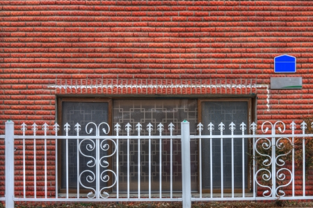 White iron fence and red brick wall of the house photo