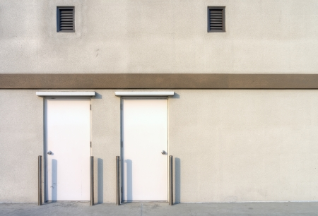 A concrete wall with 2 metal doors and 2 air passages photo