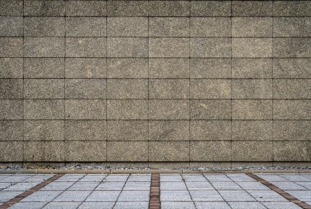 Granite tiles wall and concrete block pavement photo