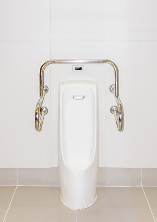 urination: A male urinal with iron bar for accessibility in restroom