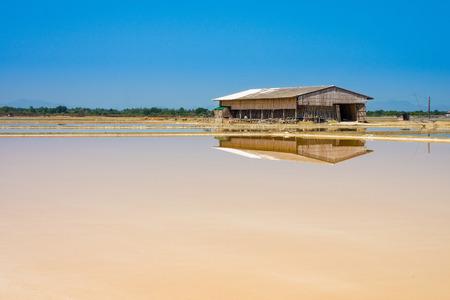 salina: Dunaliella salina in salt evaporation pond and wooden storehouse for salts storage in Thailand Stock Photo