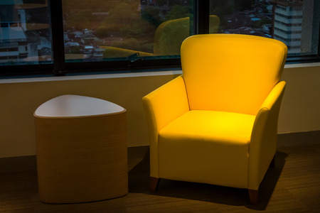 Yellow leather sofa and side wooden table Stock Photo