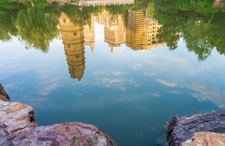 The reflection of dignified ancient tower in a pond of Xingguo Temple photo