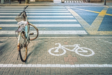 parking lot: Old bicycle with bicycle symbol on bicycle parking lot at roadside in a town of China Stock Photo