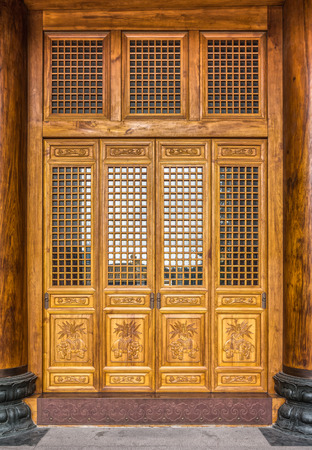 The antique Chinese wooden carved doors of the place of worship in Jing photo