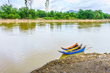 motorboats: The colorful vintage wooden motorboats in the Takua Pa river of Southern Thailand