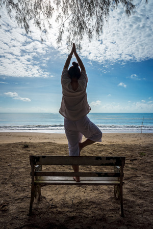 vriksasana: Woman poses outdoor Vriksasana or Tree Pose yoga on the beach Stock Photo