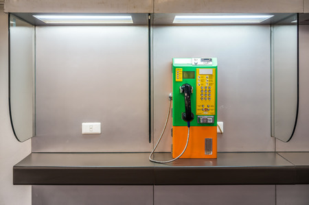 payphone: A public payphone is located in a telephone booth with pre-payment by inserting coins or card