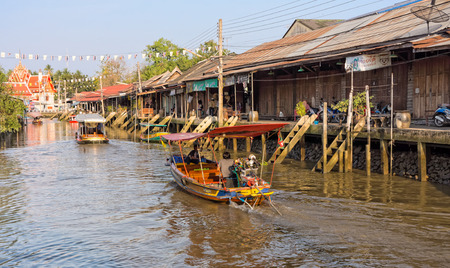 boatman: The traditional motorboat and riverside Thai village at Amphawa district in countryside of Thailand