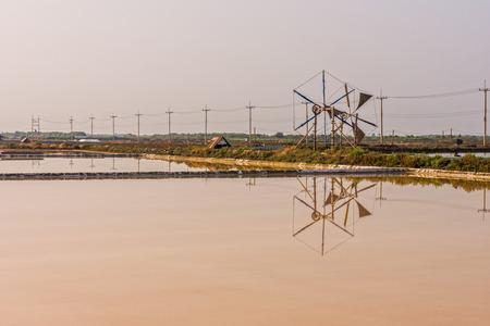 evaporacion: Vista del paisaje del estanque de evaporaci�n de sal y rueda de viento en Tailandia Foto de archivo