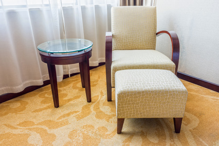 upholster: Cream armchair with stool and side circle wooden table with glass on top in a room