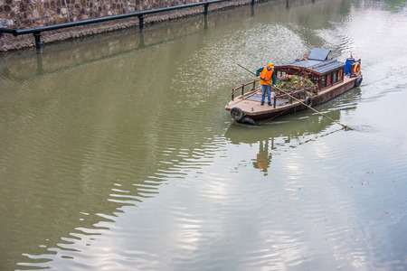 refuse: A waste collector is collecting refuse from a river