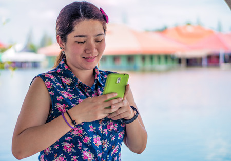 handheld device: Happy woman is playing her mobile phone to communication with another people Stock Photo