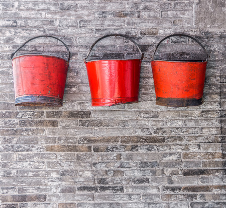 watertight: The old red metal buckets for decoration on the brick wall