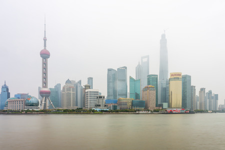 pudong district: SHANGHAI, CHINA - MARCH 28, 2014: A foggy day in Pudong landmarks. Pudong is a district of Shanghai, China, located east of the Huangpu River across from the historic city center of Shanghai in Puxi.