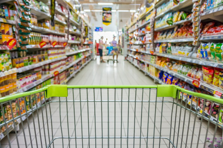 grocery basket: Shopping with shopping cart in snack department of supermarket