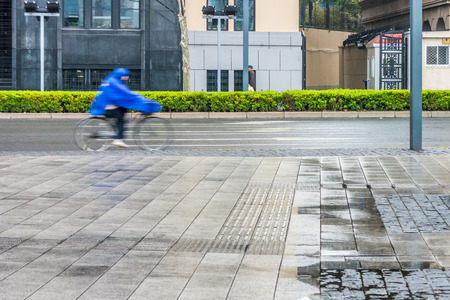 mackintosh: A bicyclist with bicycle at roadside in city after rainy day Stock Photo