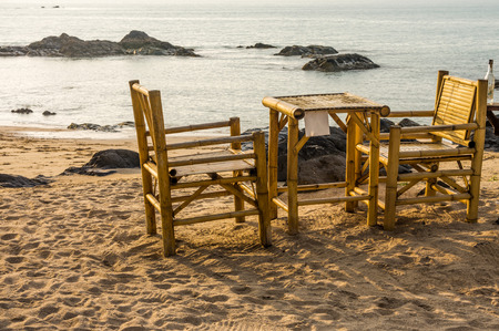 southern thailand: Bamboo chairs and table on Pak Weep beach in Southern Thailand in the evening Stock Photo