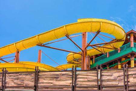 slider: The yellow water slider at outdoor amusement park Editorial