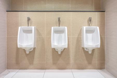 toilete: Dise�o interior moderno de urinarios de cer�mica blanca para los hombres en la nueva sala de ba�o