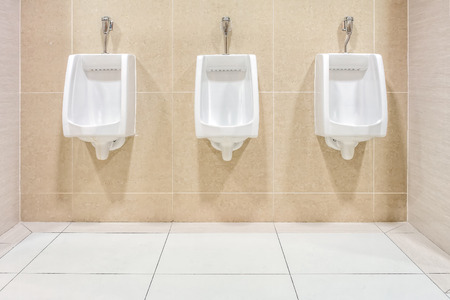 Modern interior design of white ceramic urinals for men in new toilet room