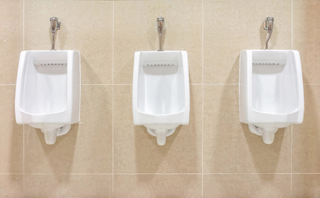 Modern interior design of white ceramic urinals for men in new toilet room photo