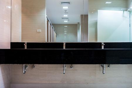 washbasins: New mirrors and ceramic granite counter washbasins in modern restroom Stock Photo