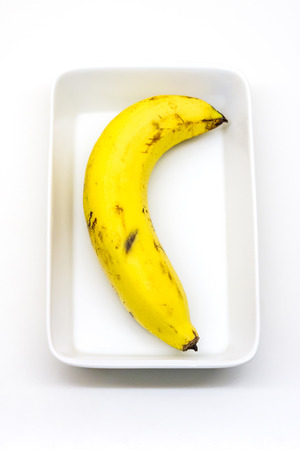 ripened: The abstract image of yellow ripened cavendish banana in a white bowl