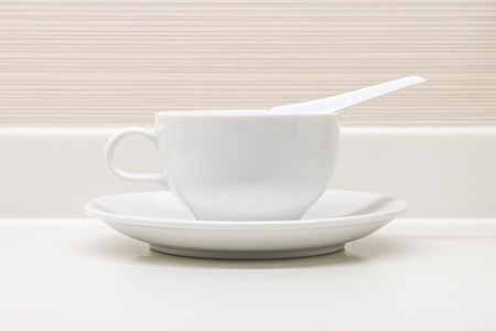 counter top: A white ceramic cup with saucer and soupspoon on counter top