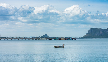 The seascape view of boats, concrete pier and mountain island at Prachuap Khiri Khan bay, Southern Thailand photo