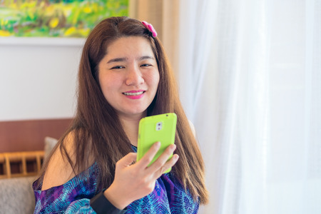 handheld device: Happy asian woman is playing and chatting on her mobile phone to communication with another people