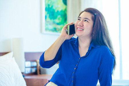 handheld device: Happy Thai lady is talking on her mobile phone to communication with another people
