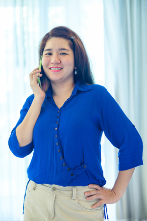 handheld device: Charming Asian woman is talking on her mobile phone to communication with another people Stock Photo