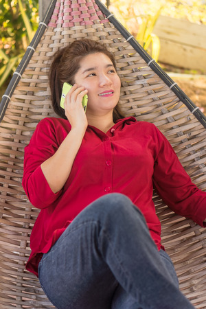 handheld device: Happy Thai girl is talking on mobile phone to communication with another people in a wicker bamboo hammock Stock Photo