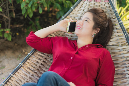 handheld device: Beautiful Asian woman is talking on mobile phone to communication with another people in a wicker bamboo hammock Stock Photo