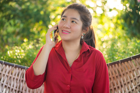 handheld device: Smiling Thai lady is talking on mobile phone to communication with another people in a wicker bamboo hammock Stock Photo