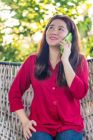 handheld device: Smiling Asian woman is talking on mobile phone to communication with another people in a wicker bamboo hammock