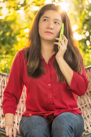 handheld device: Beautiful Thai lady is talking on mobile phone to communication with another people in a wicker bamboo hammock
