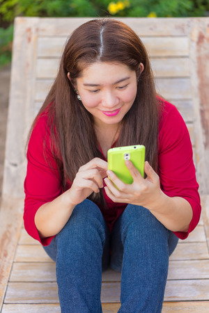 handheld device: Happy asian woman is playing and chatting on her mobile phone to communication with another people in sunbed wooden seat Stock Photo