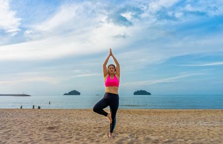 vriksasana: Fat Thai woman poses a standing asana yoga or vriksasana or tree pose on the beach Stock Photo