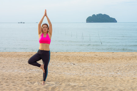 vriksasana: Thai woman poses a standing asana yoga or vriksasana or tree pose on the beach Stock Photo