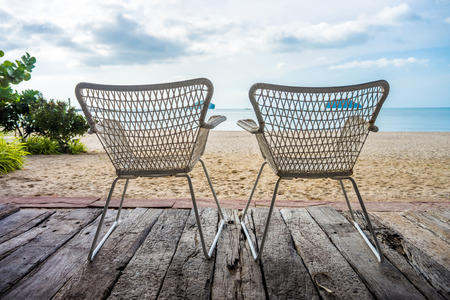 log deck: Khlong Wan beach with silhouette of twin wicker chairs on wooden log deck in Prachuap Khiri Khan province Thailand