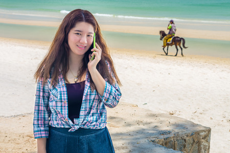 Pretty Asian woman is talking on mobile phone to communication with another people at Hua Hin beach in Prachuap Khiri Khan Province Southern Thailand photo