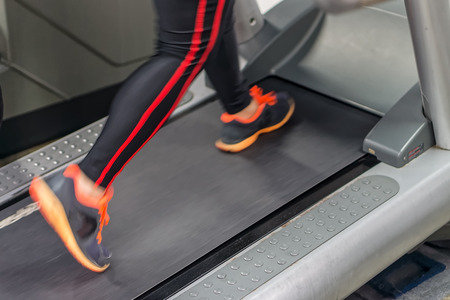 A person is running hard on a treadmill to get a good workout in fitness center room