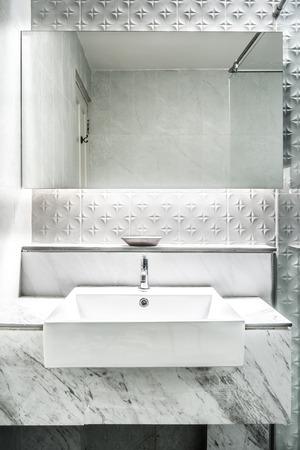 New mirror and ceramic washbasins on granite counter in modern restroom photo