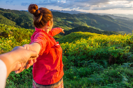 swain: Red cloth woman leads her lover by the hand on mountain of Tithonia diversifolia field in the evening Northern Thailand Stock Photo