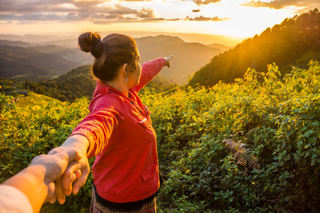swain: Natural landscape view of Sunset and red cloth lady leads her lover by the hand on mountain of Tithonia diversifolia field in the evening Northern Thailand Stock Photo
