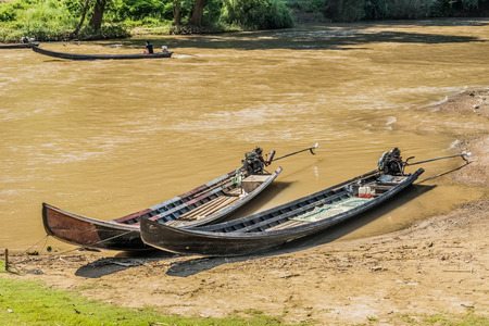 turbid: Long tail wooden motorboats in river are vintage water transportation in Thailand Stock Photo