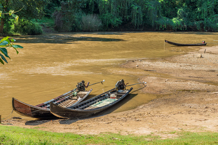 water transportation: Long tail wooden motorboats in river are vintage water transportation in Thailand Stock Photo
